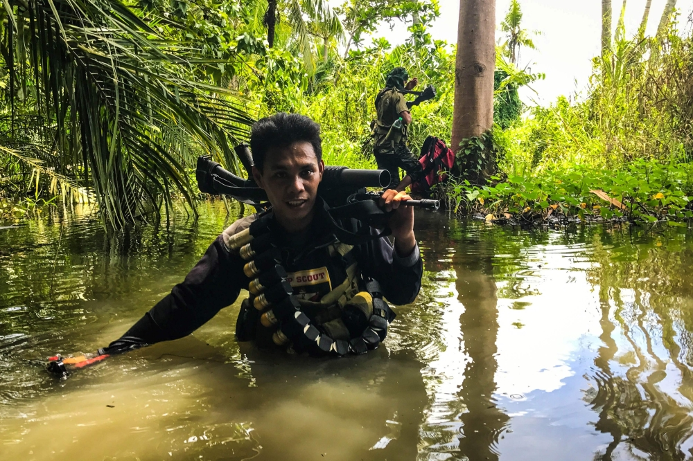 A member of the Moro Islamic Liberation Front (MILF) wades through a flooded farm on his way to the front-line in Datu Salibo town, Maguindanao province, in southern island of Mindanao, Philippines, on Tuesday. — AFP