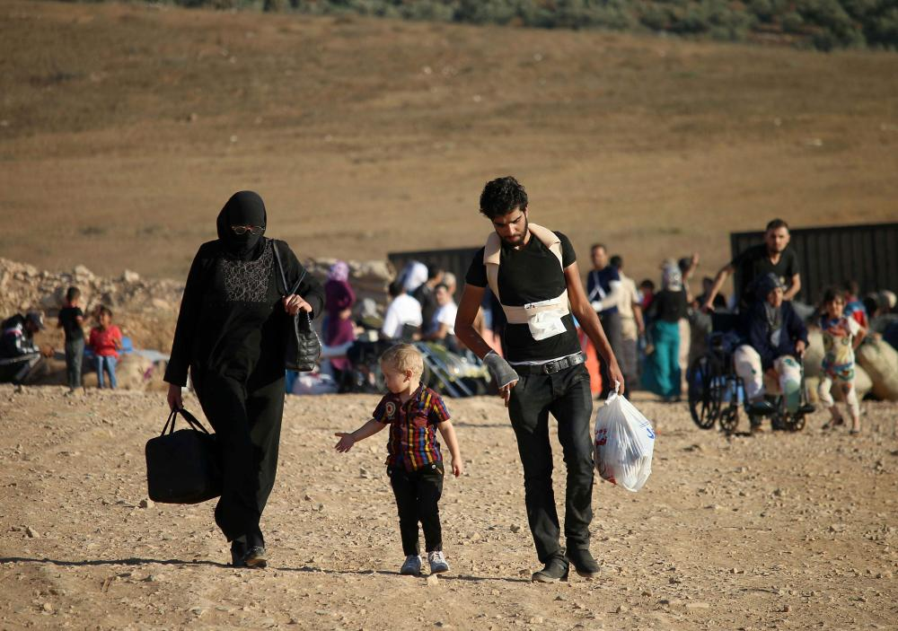 Syrians walk carrying their belongings after crossing the Syria-Jordan border near the town of Nasib as they return to their homes following a US-Russia ceasefire brokered in three southern provinces, Daraa, Quneitra, and Sweida earlier in the year. — AFP