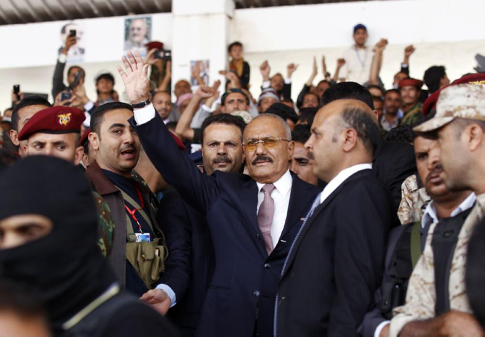 Yemen's ex-president Ali Abdullah Saleh (center) waves after giving a speech addressing his supporters during a rally as his General People's Congress party marks 35 years since its founding, at Sabaeen Square in the capital Sanaa, Thursday. — AFP