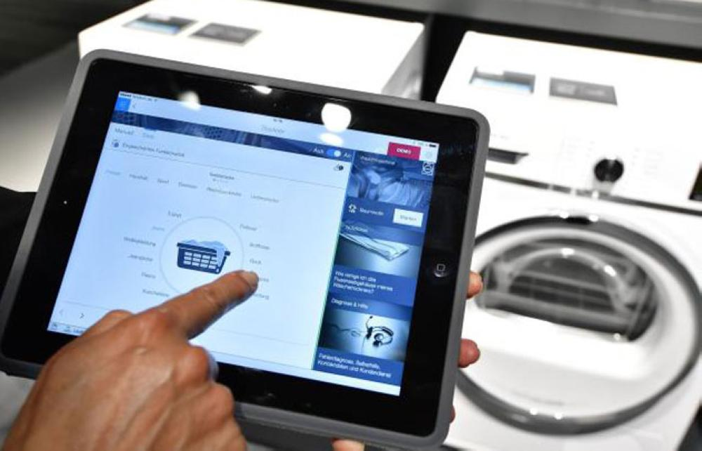 A fair worker uses a tablet to operate a tumble dryer during a demonstration how to operate smart controlled household appliances for
