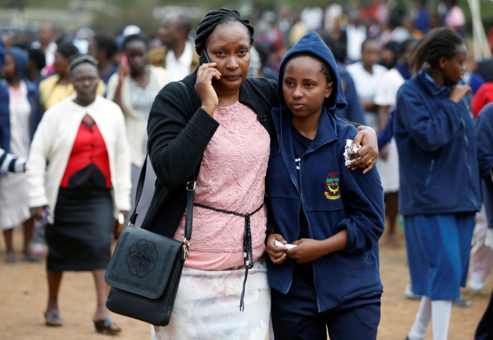 A parent embraces a student following a fire which burnt down one dormitory of Moi Girls school in Nairobi, Kenya on Saturday. — Reuters
