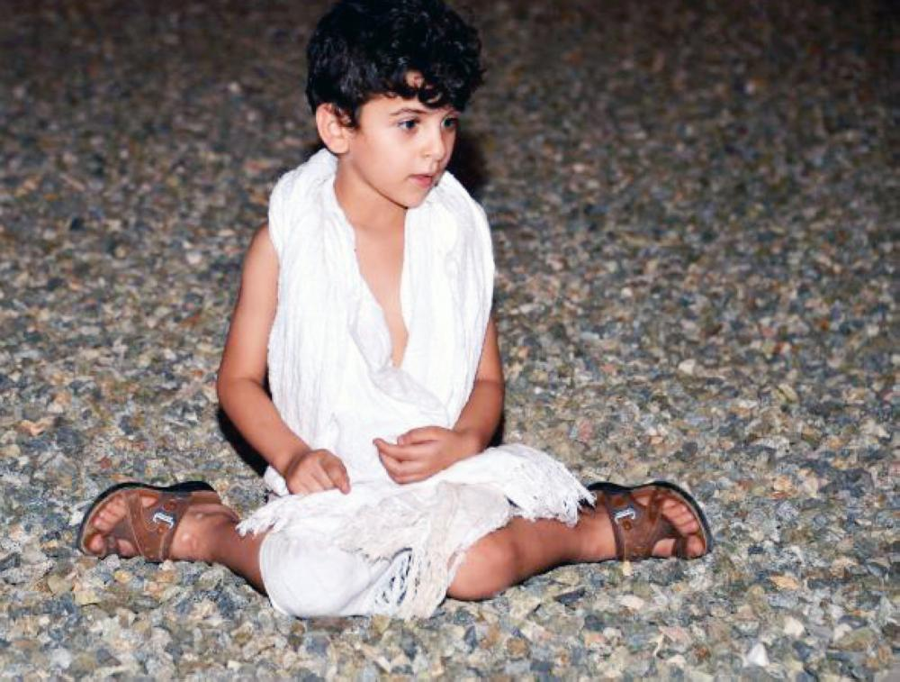 A young pilgrim picks up stones from Muzdalifah to throw them at the devil in the Jamarat area in Mina. — courtesy photo