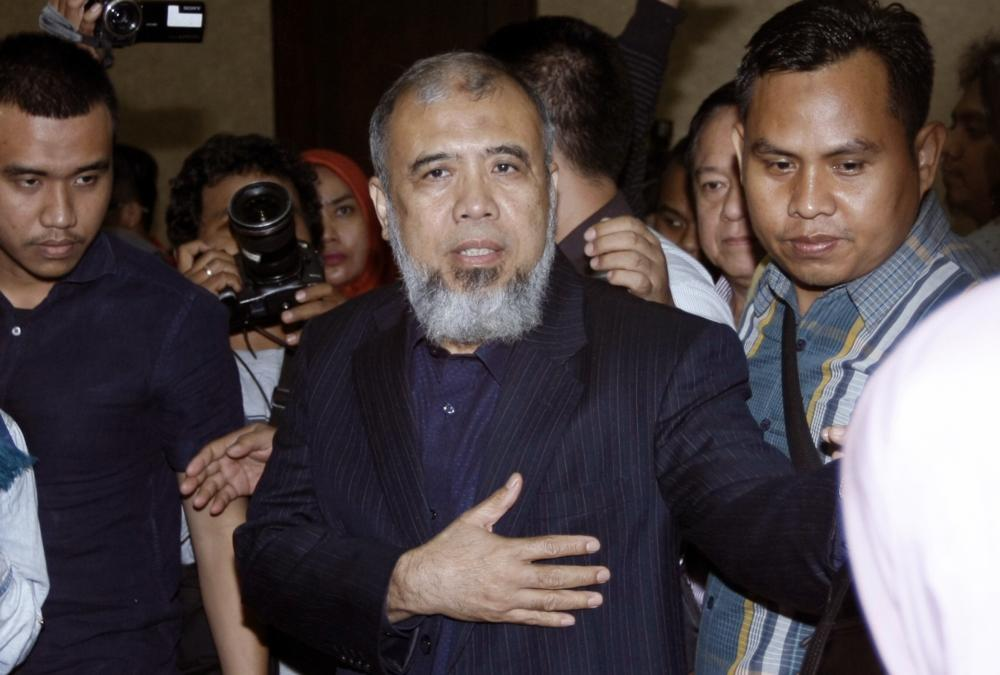 Constitutional Court Judge Patrialis Akbar (center) is escorted by security officers after his sentencing hearing at the Corruption Court in Jakarta, Monday. — AP