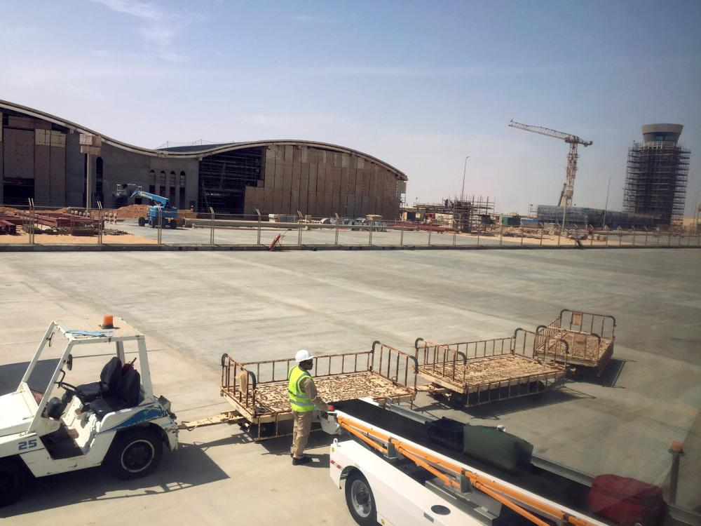 A worker unloads bags at the under-construction Duqm International Airport in Duqm, Oman, on August 21, 2017.  — Reuters