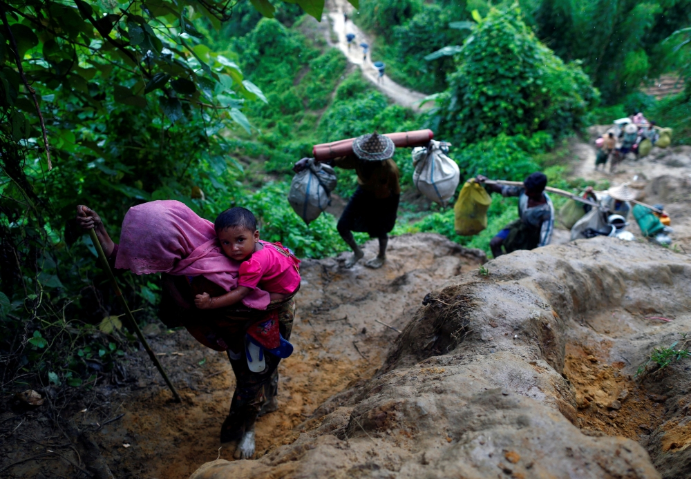 Rohingya refugees climb up a hill after crossing the Bangladesh-Myanmar border in Cox's Bazar, Bangladesh, on Friday. — Reuters