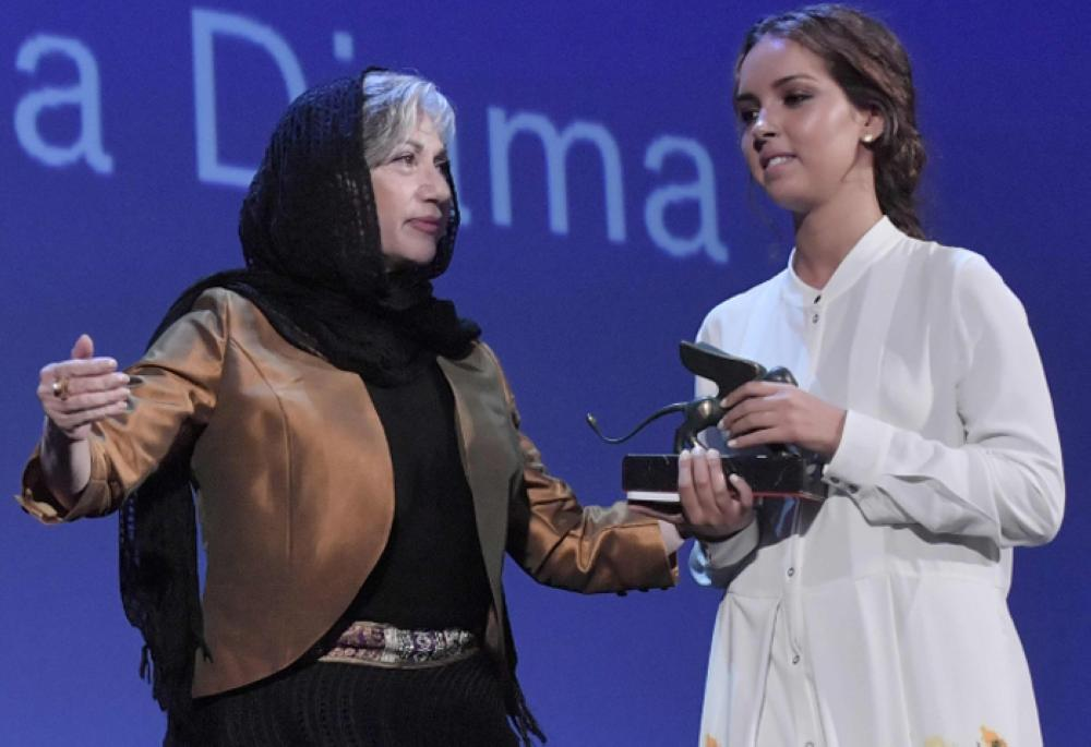 Actress Lina Khoudri, right, receives the Orizzonti Award for Best Actress for her character in the movie