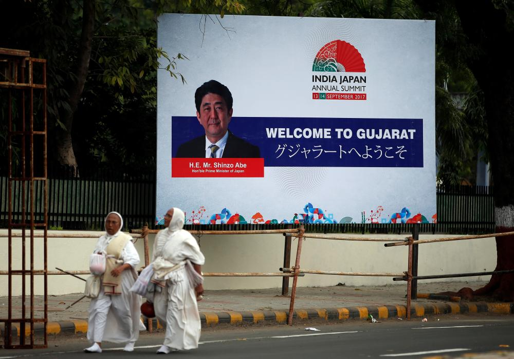 Women walk past a billboard featuring Japanese Prime Minister Shinzo Abe ahead of Abe's visit, in Ahmedabad, India, on Monday. — Reuters