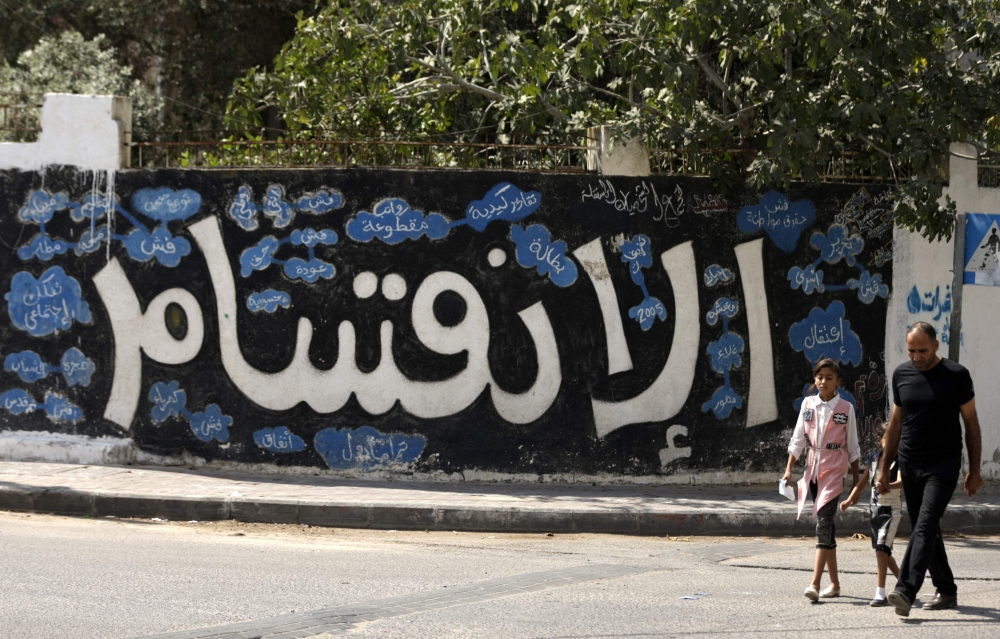 A Palestinian man and his daughter walk past a graffiti reading in Arabic ''Division'' in Gaza City on Sunday after Hamas announced it had agreed to steps toward resolving a decade-long split with the Fatah movement and was ready to hold elections. — AFP