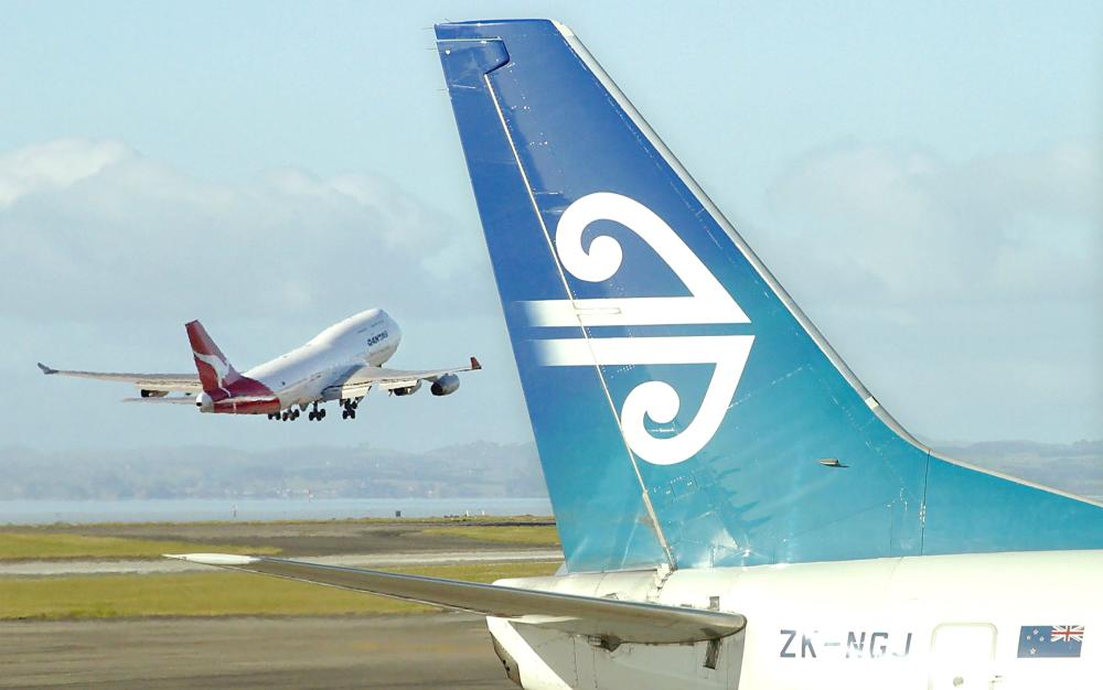 An Air New Zealand Boeing 737 sits at a departure gate while an Australian Qantas Boeing 747-400 takes-off from Auckland Airport in Auckland in this Dec. 5, 2003 file photo. — AFP