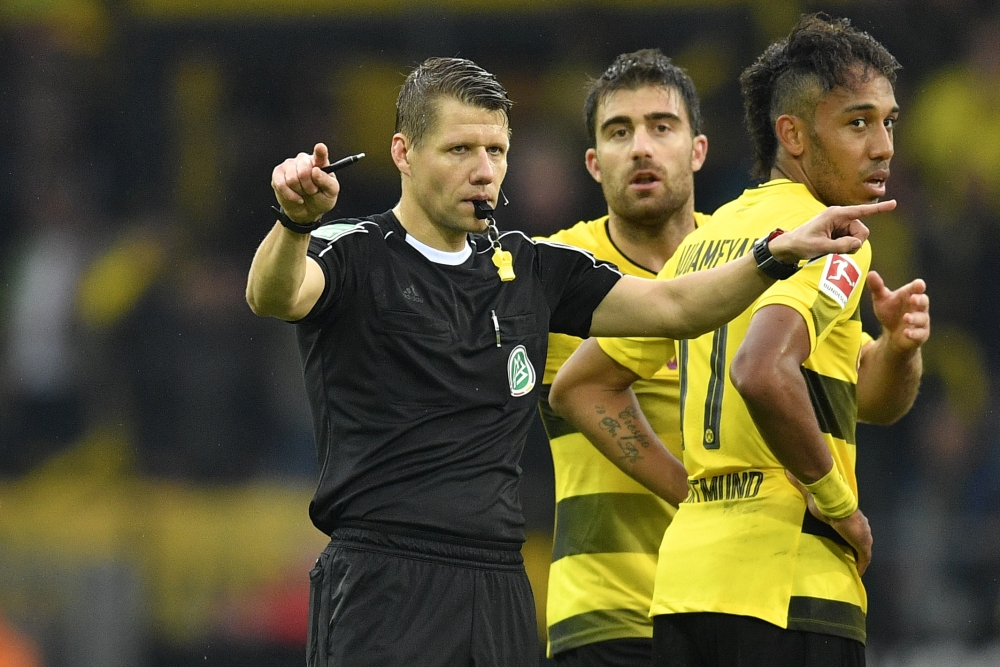 Referee Patrick Ittrich, left, asks for a video decision after a goal by Sokratis, rear center, during the German Bundesliga soccer match between Borussia Dortmund and FC Cologne in Dortmund, Germany. Dortmund defeated Cologne with 5-0, Cologne protests because of a disputed video decision. — AP