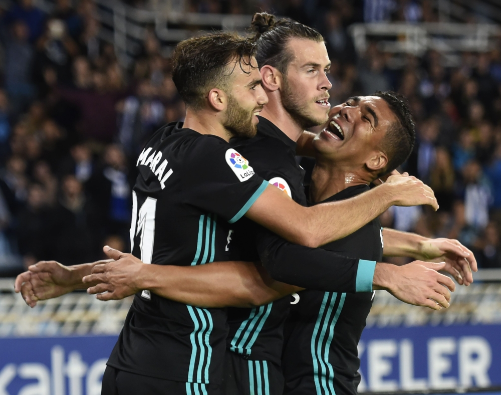 Real Madrid's forward from Wales Gareth Bale (C) celebrates his team's third goal with Real Madrid's midfielder from Brazil Casemiro (R) and Real Madrid's forward from Spain Borja Mayoral during the Spanish league football match against Real Sociedad at the Anoeta stadium in San Sebastian on Sunday. — AFP