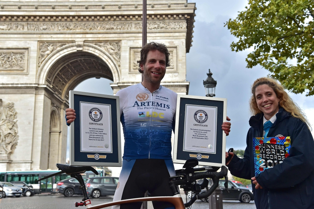 British cyclist Mark Beaumont poses for pictures with Guinness World Records certificates after arriving at the Arc de Triomphe in Paris on Tuesday to complete his tour around the world. - AFP