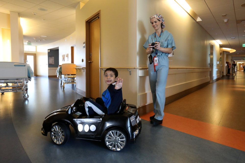 Doctor Daniela Carvalho controls Jonathan Jauregui, 7, remotely as Rady Children's Hospital unveil a program that uses remote control cars, donated by the local police officers charity, to take young patients to the operating room, in San Diego, California on Wednesday. - Reuters