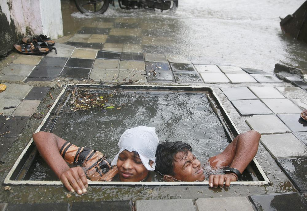 Municipal workers try to retrieve the lid of a manhole to prevent pedestrians from falling in, in Mumbai, India, on Wednesday. — AP