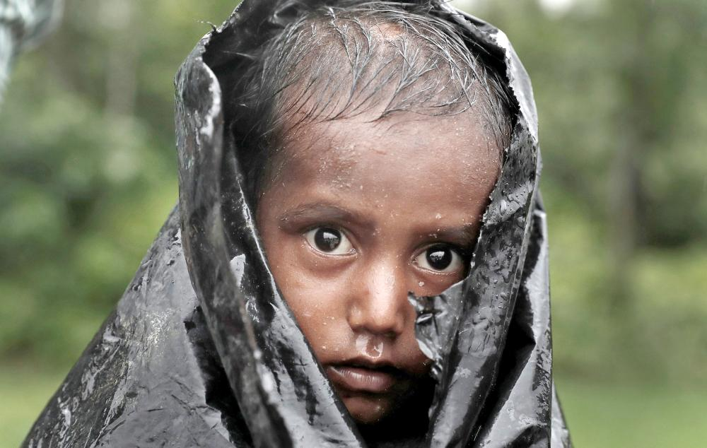 A Rohingya refugee boy waits for aid in Cox's Bazar, Bangladesh, on Wednesday. — Reuters