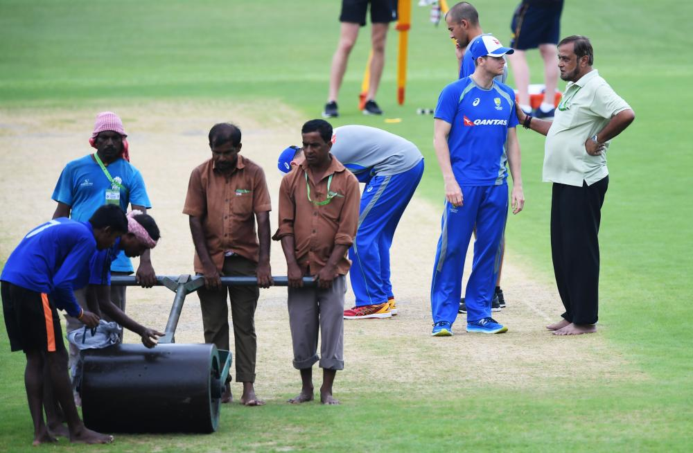 Australia's captain Steve Smith (2nd R) talks with Indian groundsman Sujan Mukherjee as groundstaff prepare the pitch ahead of a training session for the forthcoming One-Day International match against India at the Eden Gardens Cricket Stadium in Kolkata Wednesday. — AFP