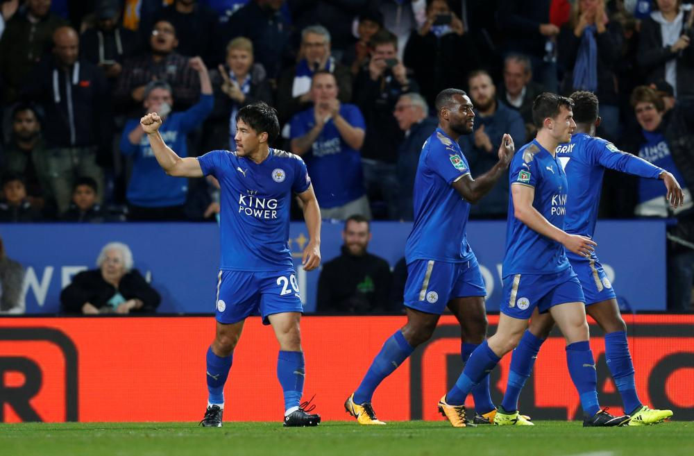 Leicester City's Shinji Okazaki (L) celebrates scoring their first goal with teammates against Liverpool during their League Cup match in Leicester Tuesday. — Reuters