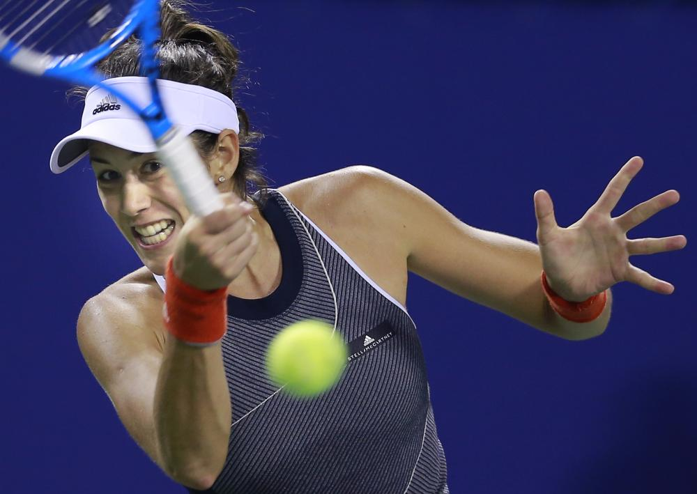 Garbine Muguruza of Spain returns a shot to Monica Puig of Puerto Rico during their second round match of the Pan Pacific Open Tennis Tournament in Tokyo Wednesday. — AP