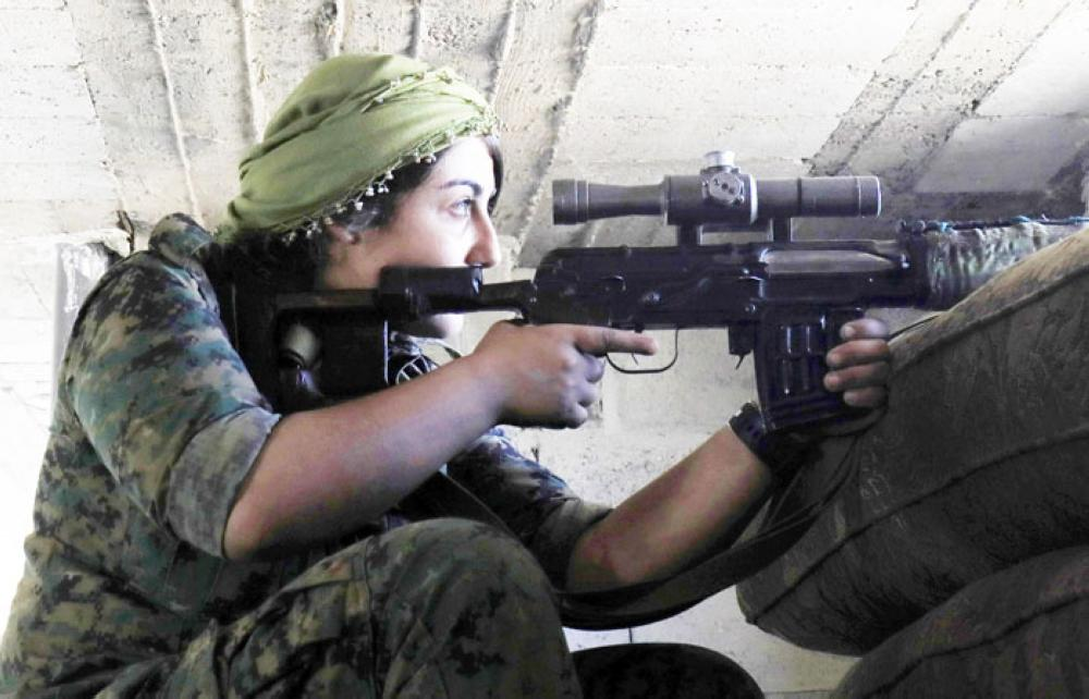 A female member of the SDF holds a position inside a building in an area close to the Old City in northern Raqqa. — AFP