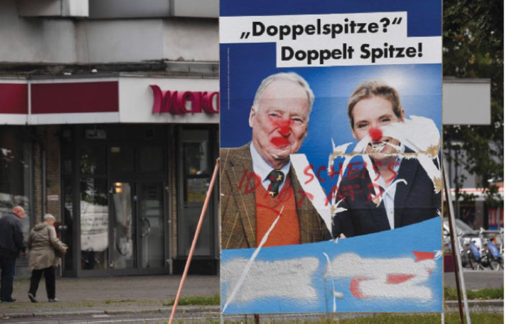 A vandalized poster from the far-right Alternative for Germany (AfD) features the party's two main candidates Alexander Gauland (left) and Alice Weidel in Berlin, ahead of parliamentary elections on Sept. 24. — AFP