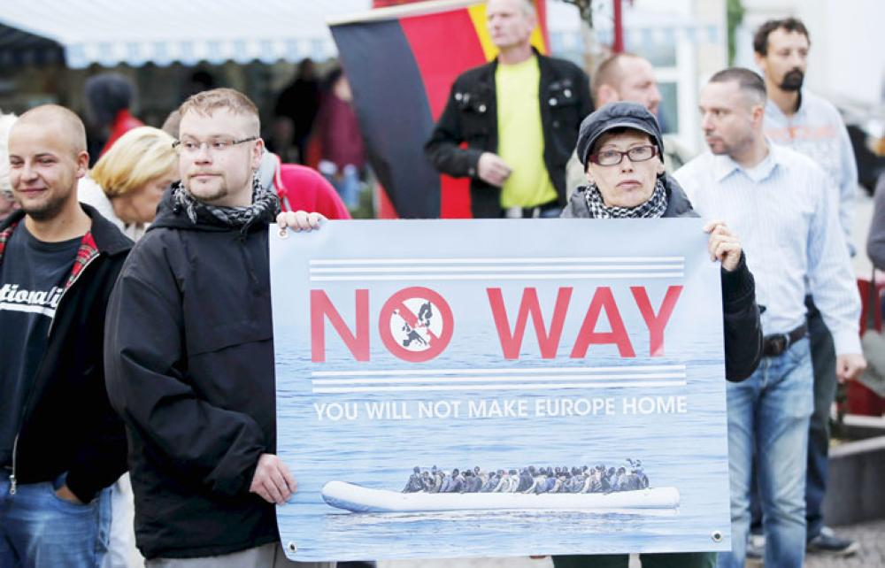 Supporters of the far-right National Democratic Party (NPD) hold a placard and a German flag during an anti-immigration march in Riesa, Germany, earlier this month. — Reuters
