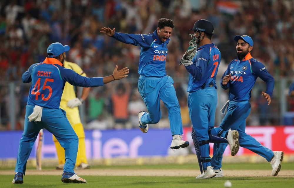 India's Kuldeep Yadav (2nd L) celebrates with his teammates after recording a hat trick during their second One-Day International against Australia in Kolkata Thursday. — Reuters
