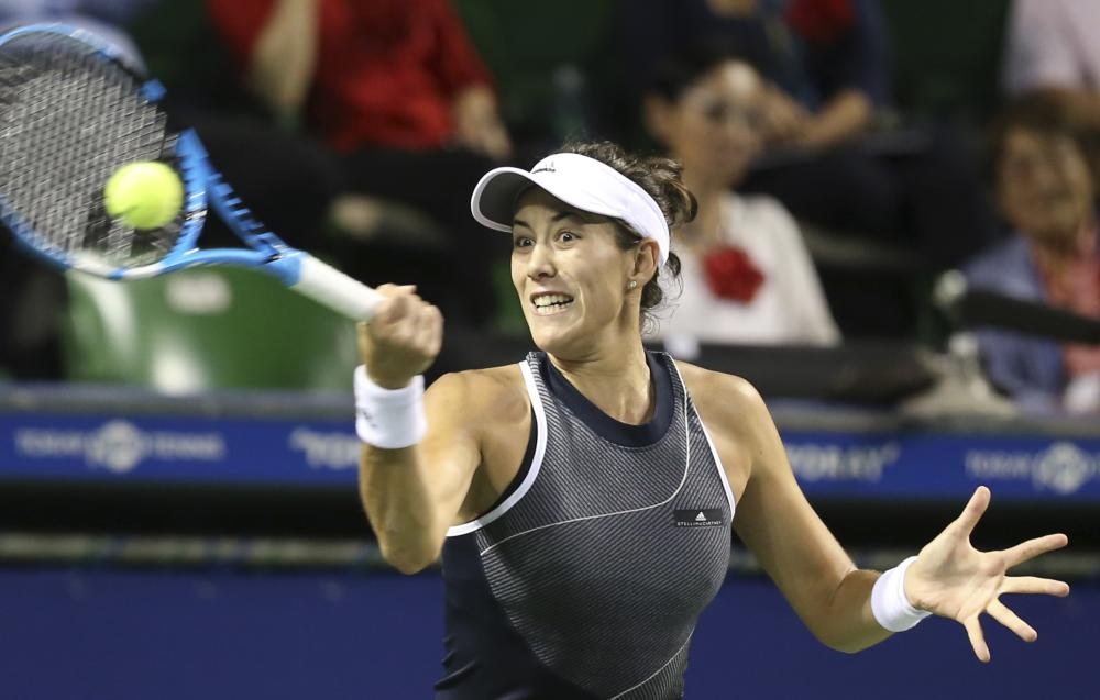 Garbine Muguruza of Spain returns a shot to Caroline Garcia of France during their quarterfinal match of the Pan Pacific Open Tennis Tournament in Tokyo Friday. — AP