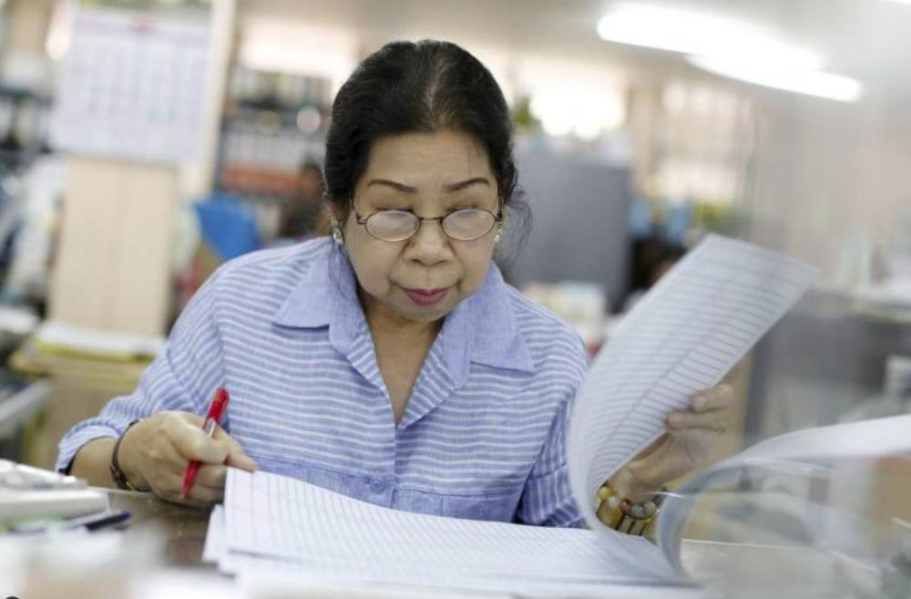 File photo shows Sunisa Hongaroon, a 67-year-old accountant, working in a transportation company in Bangkok, Thailand. — Reuters