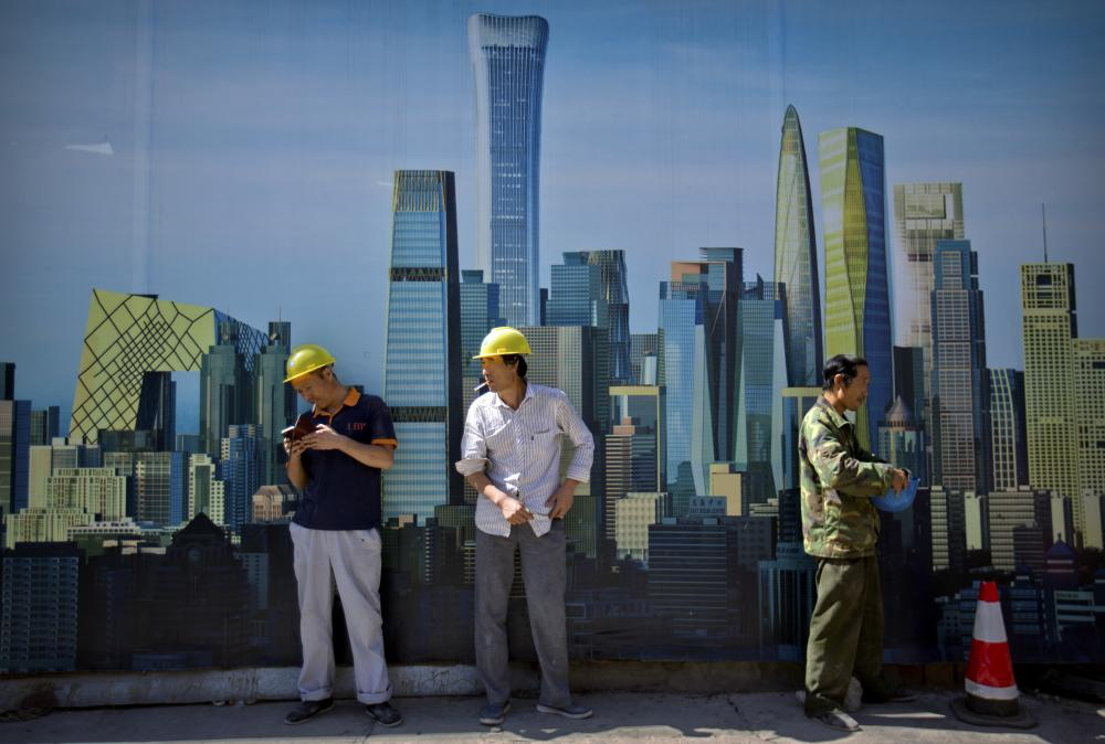 Construction workers smoke outside of a construction site in the central business district in Beijing, Friday. China's Finance Ministry on Friday criticized the cut in the Standard & Poor's rating agency's credit rating on Chinese government borrowing as a