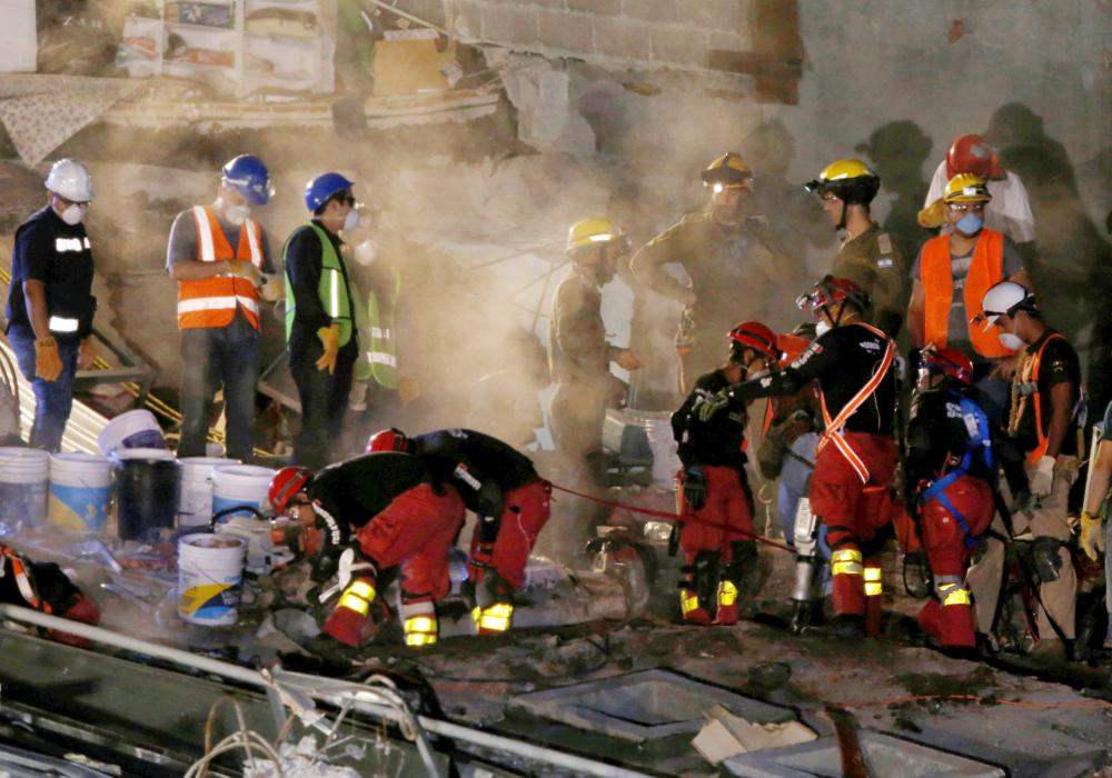 Members of rescue teams search for survivors in the rubble of a collapsed building after an earthquake in Mexico City, Mexico, on Friday. — Reuters