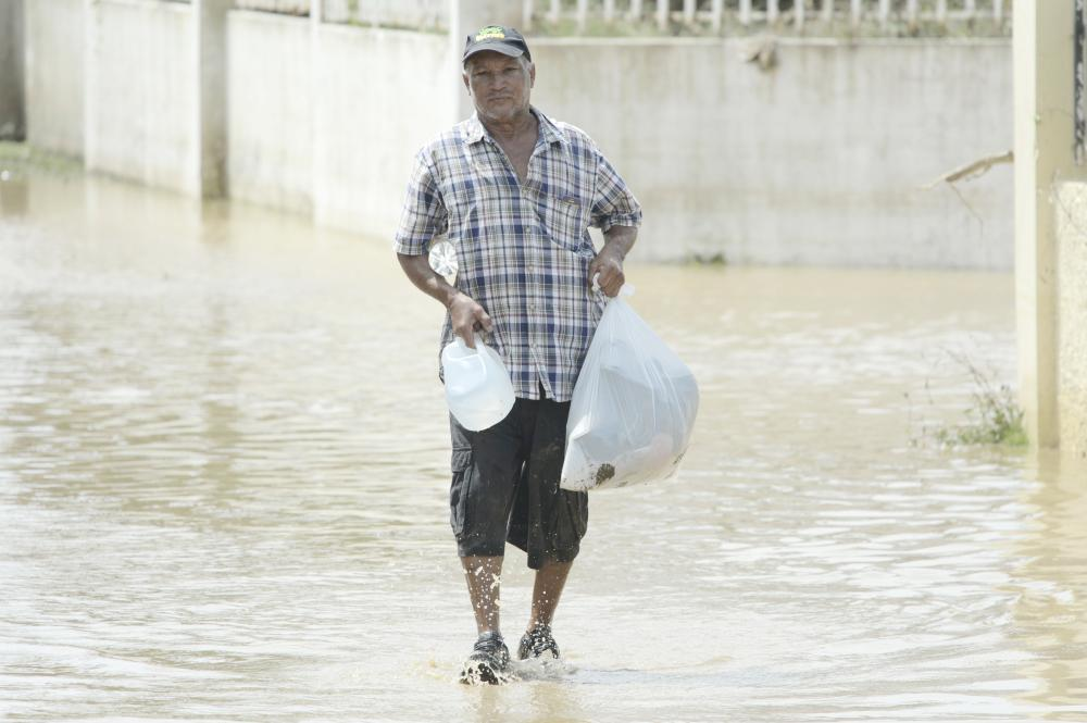 A resident carries supplies in a flooded road after the passing of Hurricane Maria, in Toa Baja, Puerto Rico, on Friday. — AP