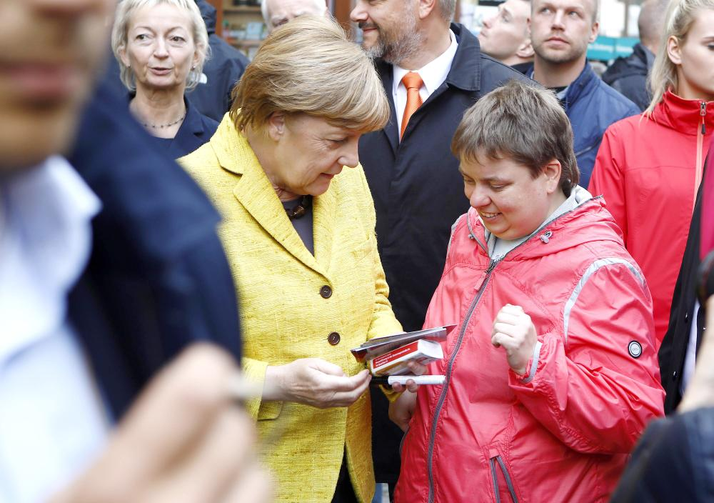 German Chancellor Angela Merkel speaks to a woman during the final Christian Democratic Union (CDU) party campaign in Stralsund, Germany, on Saturday. — Reuters