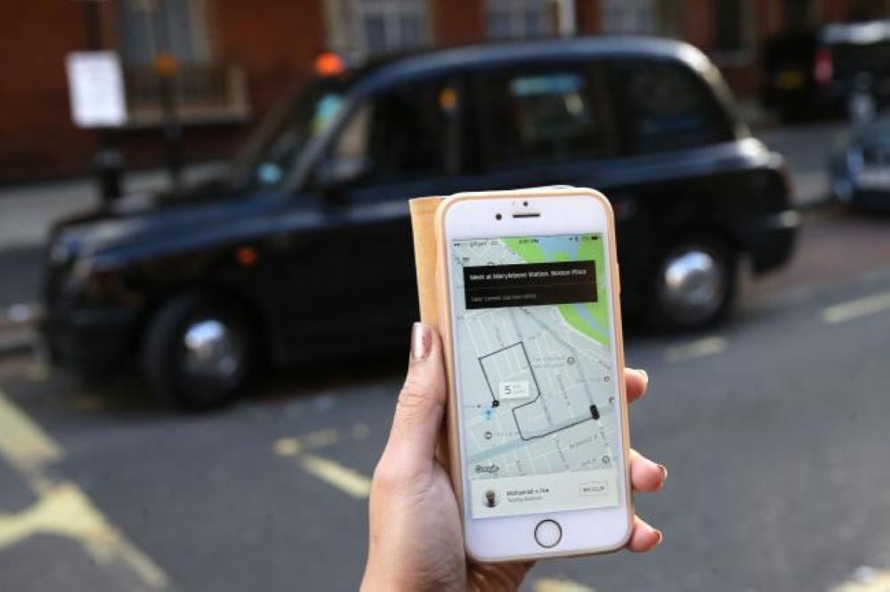 A woman poses holding a smartphone showing the App for ride-sharing cab service Uber in London on Friday. — AFP