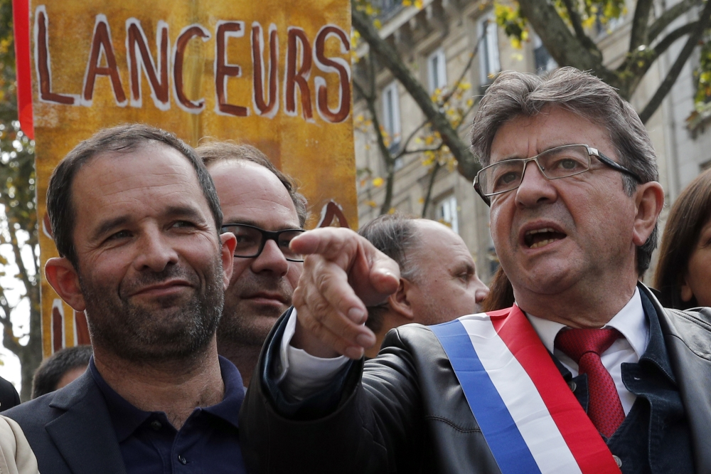 French far-left leader Jean-Luc Melenchon, right, along with former Socialist party presidential candidate Benoit Hamon, take part in a protest over the president's labor reform in Paris, France, on Saturday. — AP
