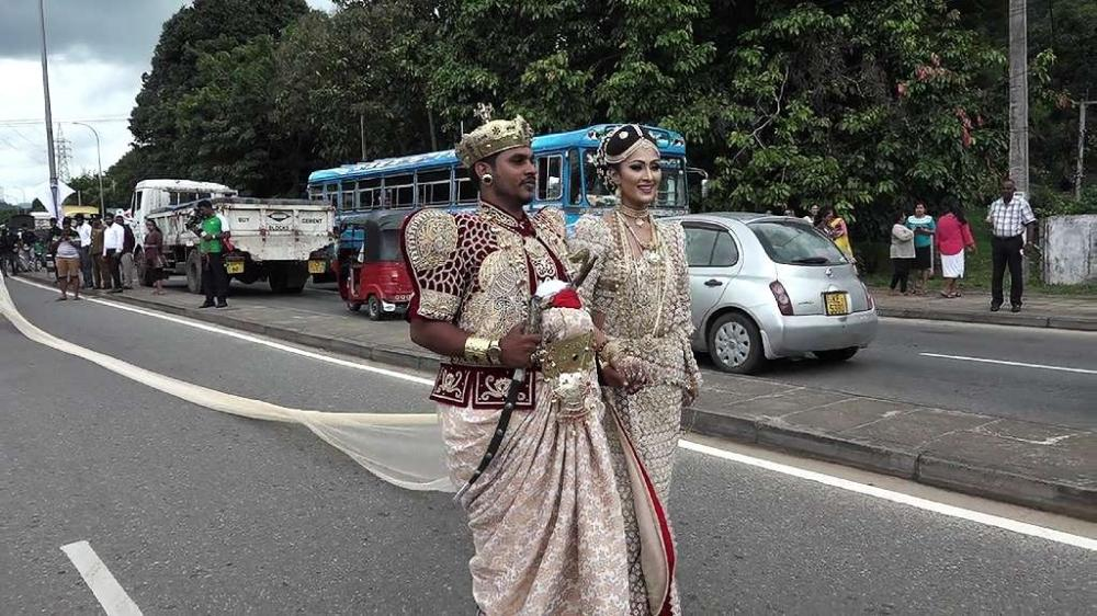 A Sri Lankan couple walk along a road as the bride attempted to set a record for the longest wedding saree extending 3.2 kilometers in the central district of Kandy on Friday. - AFP