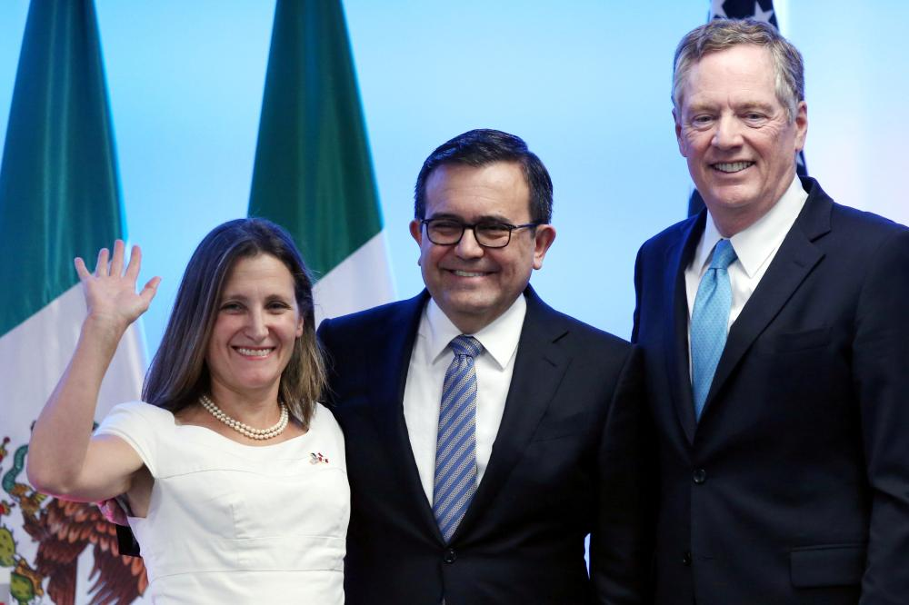 Canadian Foreign Minister Chrystia Freeland, Mexico's Economy Minister Ildefonso Guajardo and US Trade Representative Robert Lighthizer smile as they pose for a photo after addressing the media to close the second round of NAFTA talks involving the United States, Mexico and Canada at Secretary of Economy headquarters in Mexico City, Mexico. — Reuters
