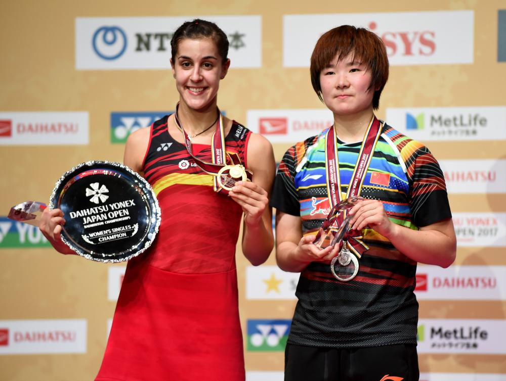 Winner Carolina Marin (L) of Spain poses with runner-up He Bingjiao of Spain at the Japan Open Badminton Championships in Tokyo Sunday. — AFP