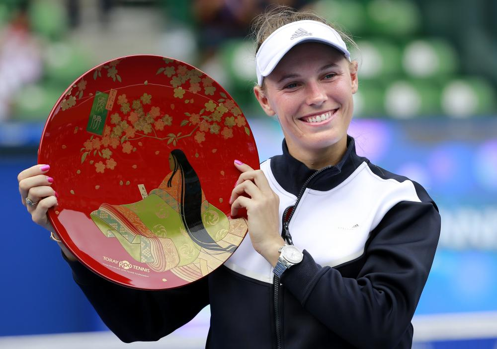 Caroline Wozniacki of Denmark poses with the winner's plate after beating Anastasia Pavlyuchenkova of Russia at the Pan Pacific Open Tennis Tournament in Tokyo Sunday. — AP
