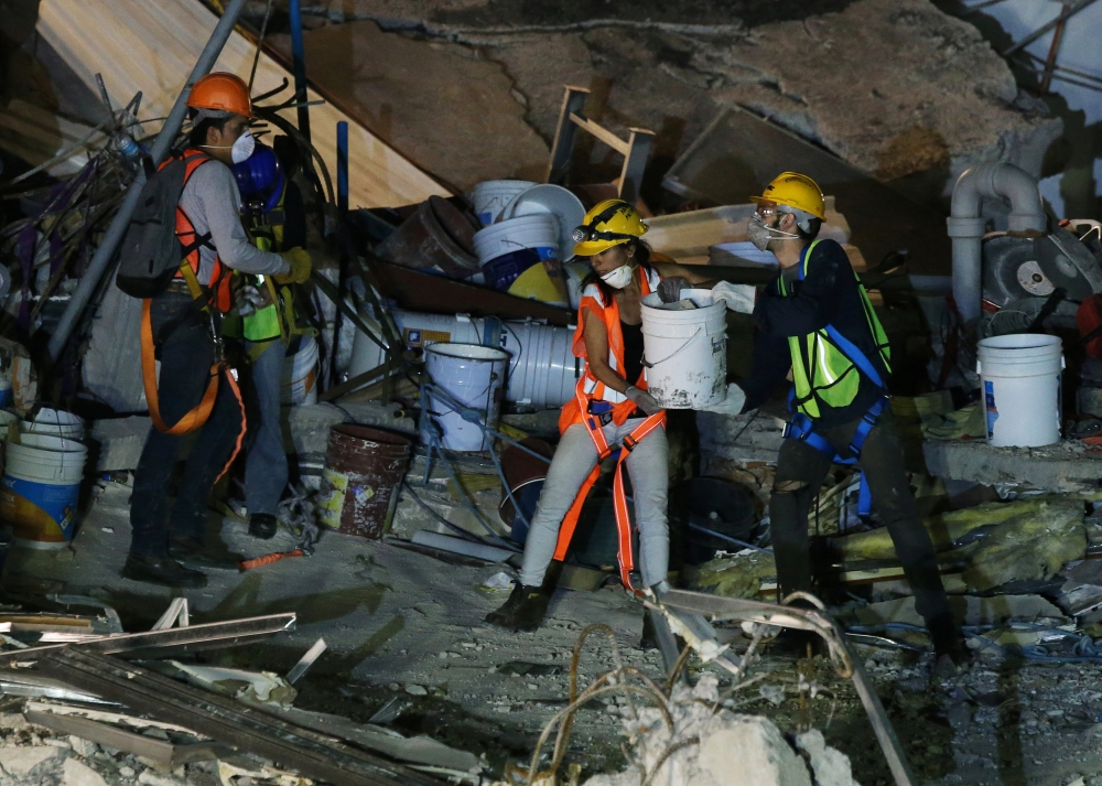 Members of rescue teams remove debris in the rubble of a collapsed building after an earthquake in Mexico City, Mexico, on Monday. — Reuters