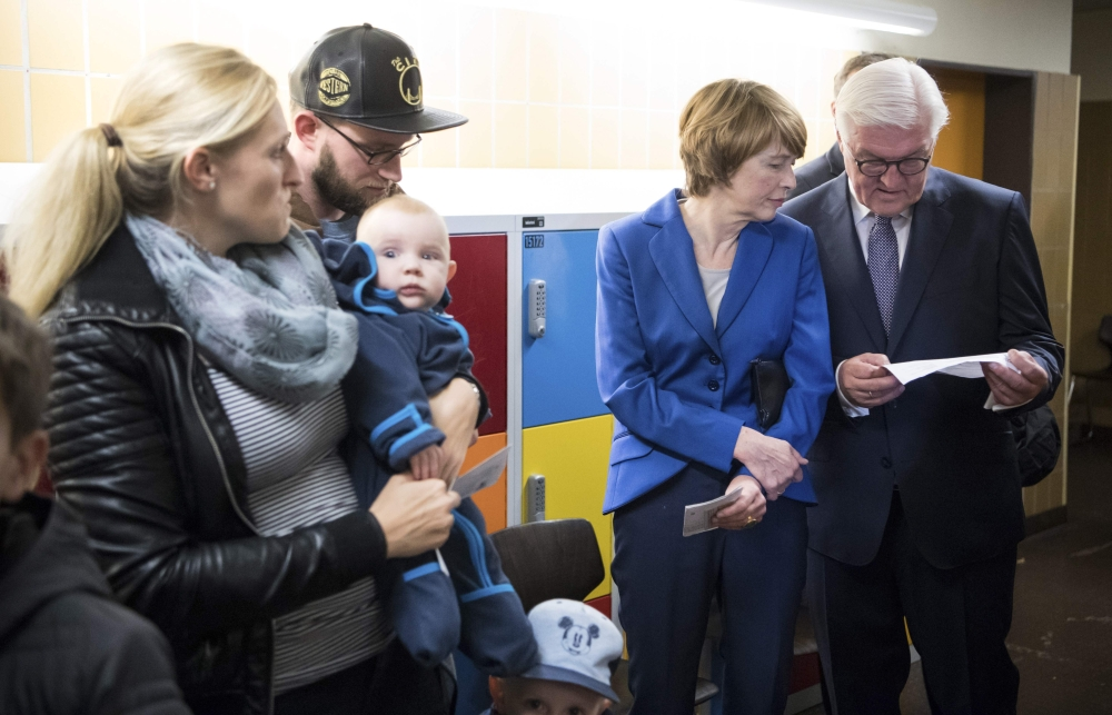German President Frank-Walter Steinmeier, right, and his wife Elke Buedenbender, second right, queue up before casting their ballots at a polling station in Berlin during general elections on Sunday. — AFP