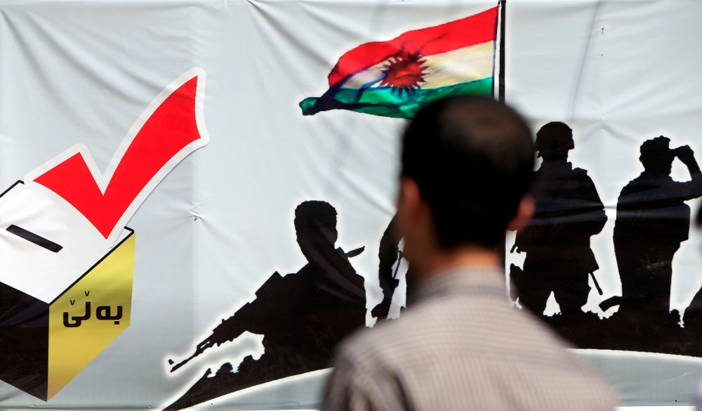 A man looks at a banner supporting the referendum for independence of Kurdistan in Irbil, Iraq, on Sunday. — Reuters