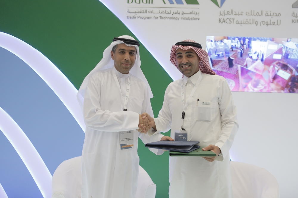 Dawood Al Shezawi (left), Chief Executive Officer of AIM Startup, shakes hands with Nawaf Al-Sahhaf, CEO of Badir Program for Technology Incubators, after the signing of agreement