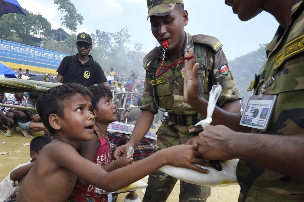 Bangladeshi soldiers distribute rice to young Rohingya refugees at the refugee camp of Balukhali near Gumdhum, Bangladesh, on Monday. — AFP