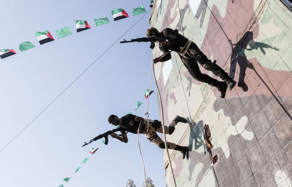 This file photo taken shows young Palestinians abseiling during a military graduation ceremony at a Hamas summer camp in Khan Yunis, in the southern Gaza Strip. — AFP