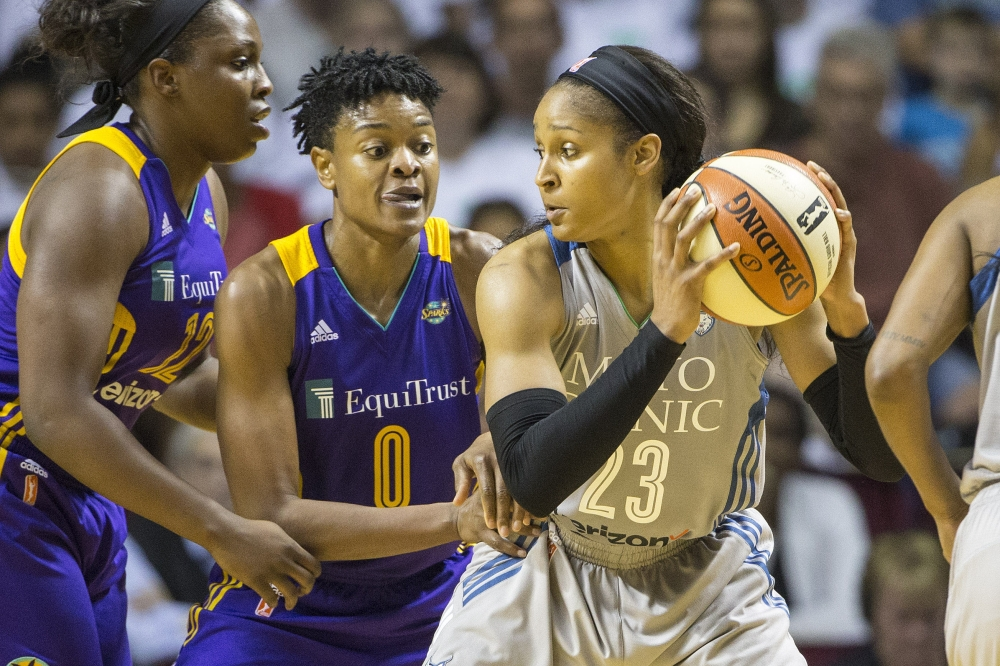 Minnesota Lynx forward Maya Moore (23) looks to pass the ball as Los Angeles Sparks guard Alana Beard (0) plays defense in the second half in Game 1 of the WNBA Finals at Williams Arena in Minneapolis, MN, on Sunday. — Reuters