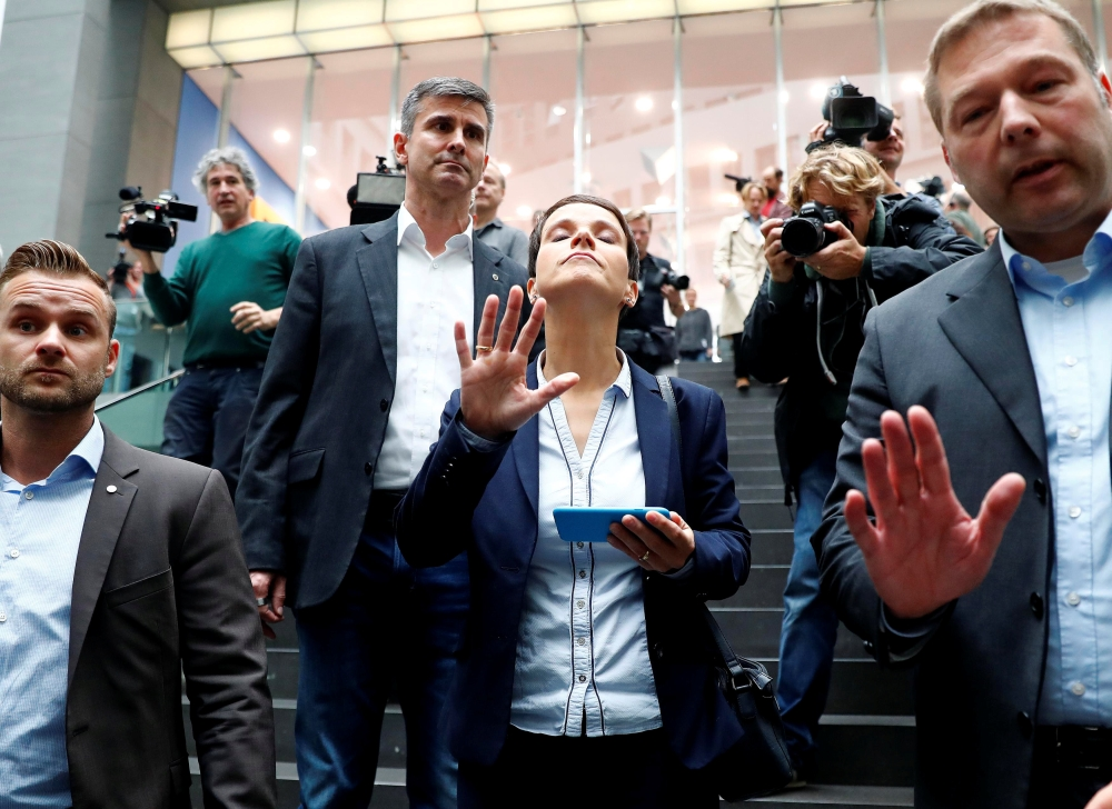 Frauke Petry, center, chairwoman of the anti-immigration party Alternative fuer Deutschland (AfD) reacts as she leaves a news conference in Berlin, Germany, on Monday. — Reuters