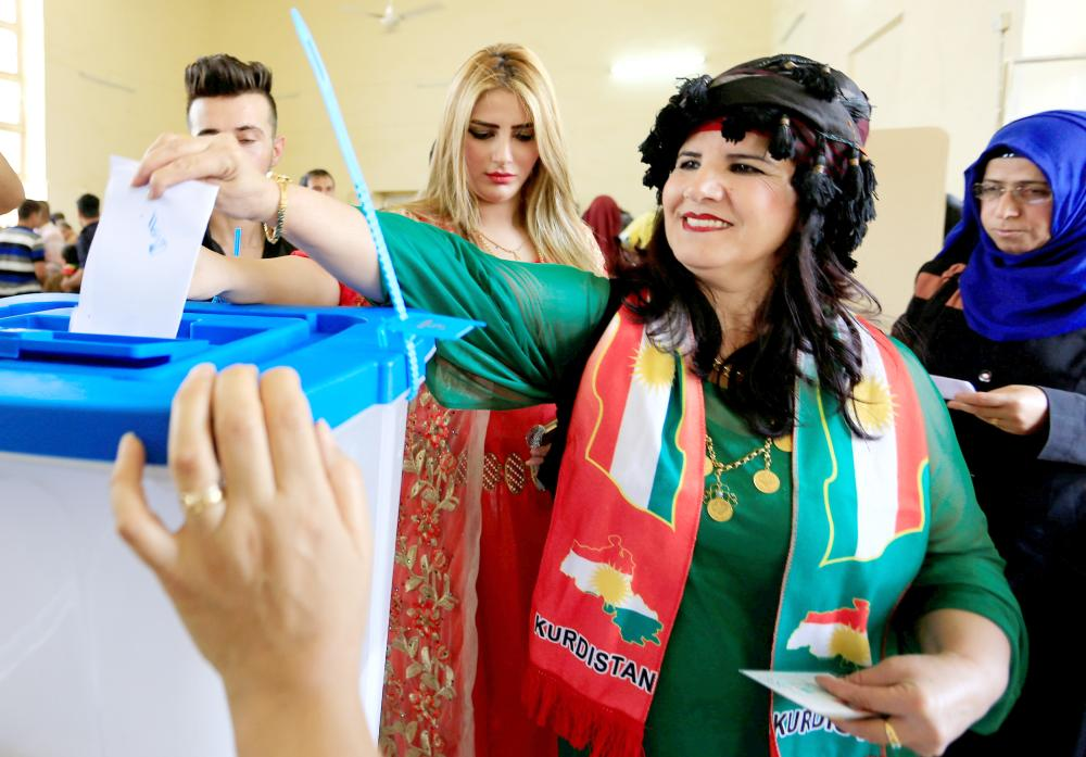 A woman casts her vote at a polling station during Kurds independence referendum in Kirkuk, Iraq, on Monday. — Reuters