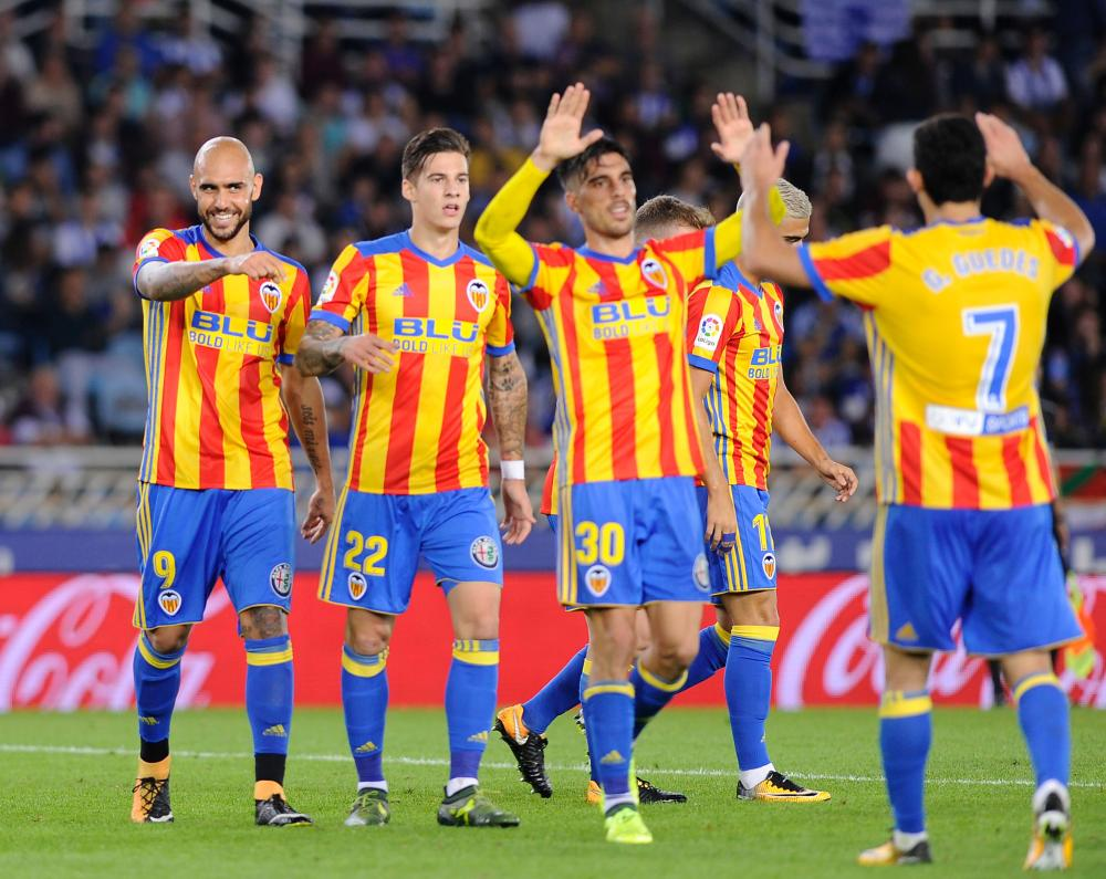 Valencia's players celebrate after forward from Italy Simone Zaza scored his team's third goal during the Spanish league football match against Real Sociedad at the Anoeta stadium in San Sebastian on Sunday. — AFP