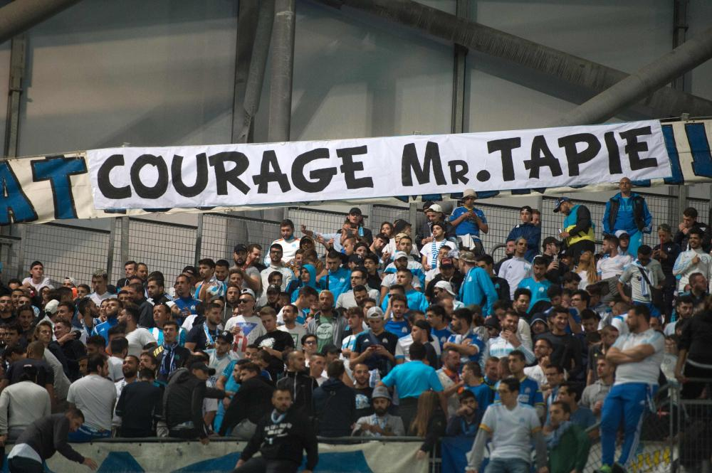 Om's fans cheer next to a banner reading