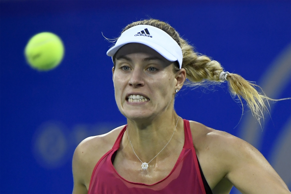 Angelique Kerber of Germany hits a return against Caroline Garcia of France during their first round women's match at the WTA Wuhan Open tennis tournament in Wuhan, in China's central Hubei province on Monday. — AFP
